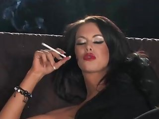 Scorching black-haired is smoking and touching her clean-shaved coochie, because it arouses her a bunch