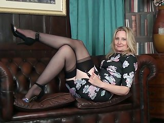 Svelte and quite leggy cougar Emma Turner undresses to pet her bald pussy